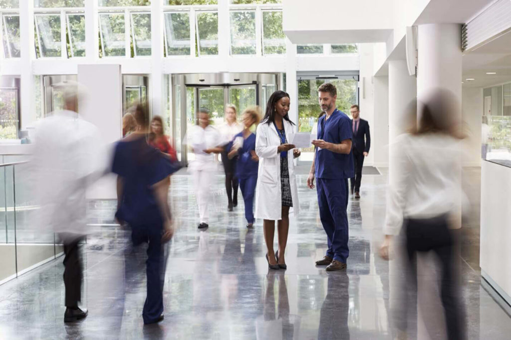A male and female doctor reviewing a chart together in the middle of a busy hospital walkway area.