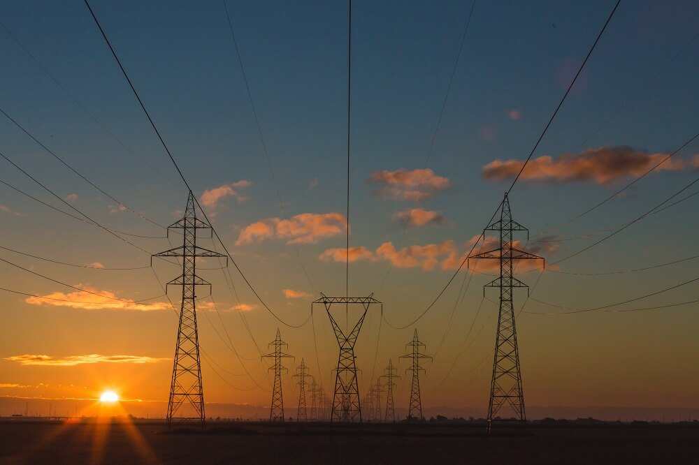 Dozens of power lines shown with the sun setting in the background.