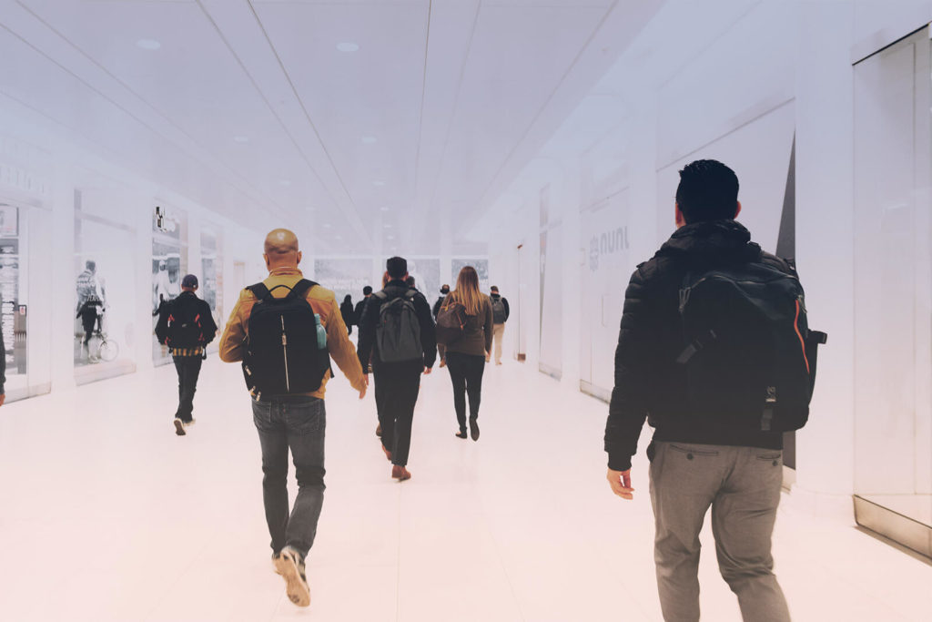 A groups of school students walking in a white hallway.