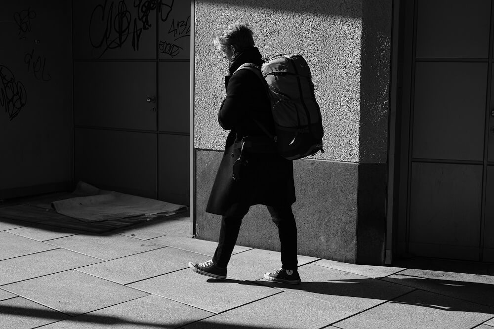 A young woman with a large backpack walking on the sidewalk during the daytime.