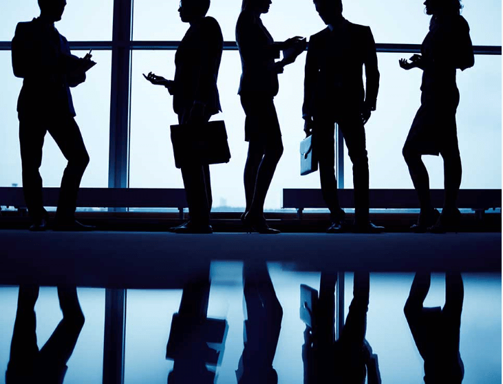 The silhouettes of 5 office employees holding suitcases and talking amongst themselves.