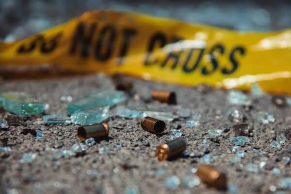 "Close-up of bullets and broken glass on the ground, with a yellow ""do not cross"" sign in the background."