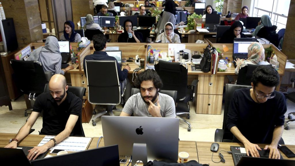 A group of employees working on their computers in an office with an open concept.
