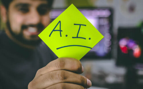 "A smiling man holds up an ""AI"" sign on a green post-it."