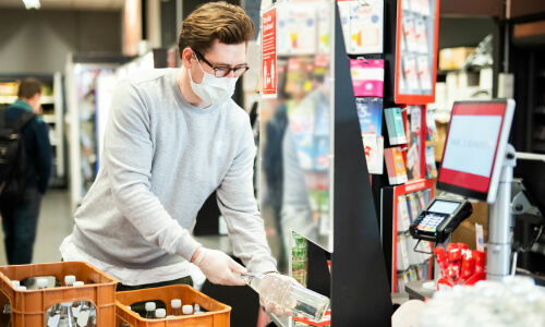 A young man wearing a face mask and gloves scans a bottle of water while in line at the grocery store.