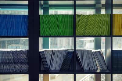 A closeup of a bookcase filled with blue, green, and yellow folders.