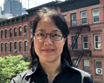 Tatiana Hanazaki smiling while standing on a balcony with NYC residential buildings in the background.